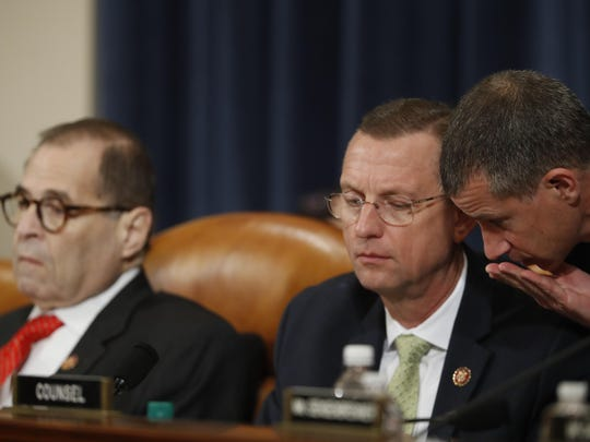 House Judiciary Committee ranking member Rep. Doug Collins, R-Ga., center, talks to Republican staff attorney Steve Castor, right, during a House Judiciary Committee markup of the articles of impeachment against President Donald Trump, Thursday, Dec. 12, 2019, on Capitol Hill in Washington. House Judiciary Committee Chairman Rep. Jerrold Nadler, D-N.Y., is left. (AP Photo/Andrew Harnik)