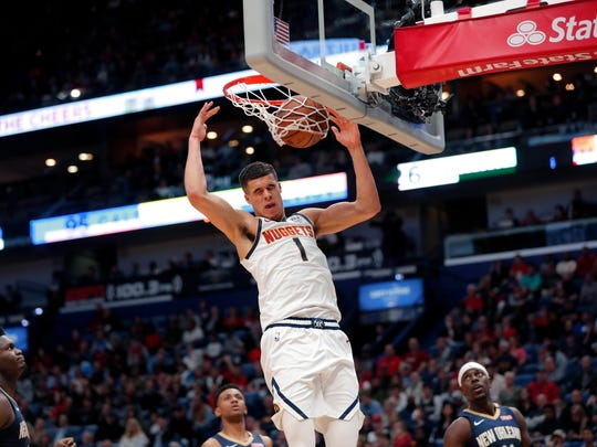 Denver Nuggets forward Michael Porter Jr. (1) slam-dunks over New Orleans Pelicans forward Zion Williamson, left, and guard Jrue Holiday, right, in the first half of an NBA basketball game in New Orleans, Friday, Jan. 24, 2020. (AP Photo/Gerald Herbert)