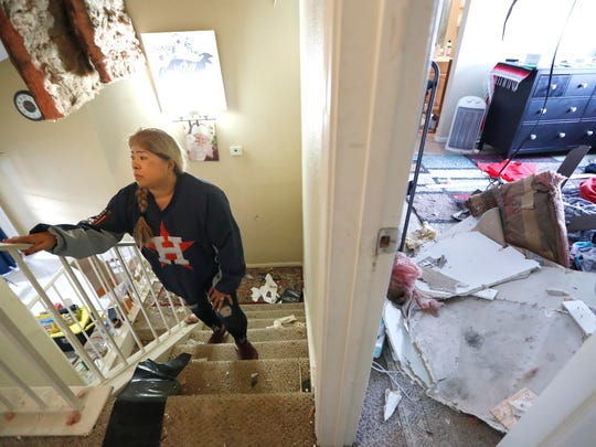 Maria Hernandez climbs her stairwell as she and her family sift through their damaged home in the Bridgeland Lane area of Houston on Sunday, after the Watson Grinding Manufacturing explosion early Friday morning.