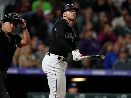 FILE - In this Sept. 28, 2019, file photo, Colorado Rockies' Trevor Story follows the flight of his walkoff home run in the 10th inning of a baseball game against the Milwaukee Brewers in Denver. The Rockies are headed to Arizona to open the team's training camp for the season ahead. (AP Photo/David Zalubowski, File)