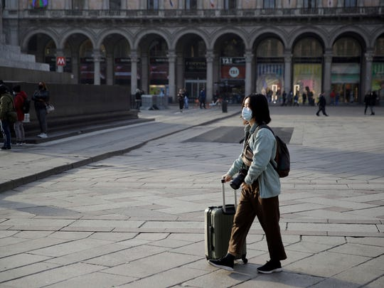 A woman wearing a sanitary mask pushes a trolley in Duomo square, Milan, Italy, Sunday, Feb. 23, 2020. A dozen Italian towns saw daily life disrupted after the deaths of two people infected with the virus from China and a pair of case clusters without direct links to the outbreak abroad. A rapid spike in infections prompted authorities in the northern Lombardy and Veneto regions to close schools, businesses and restaurants and to cancel sporting events and Masses. (AP Photo/Luca Bruno)