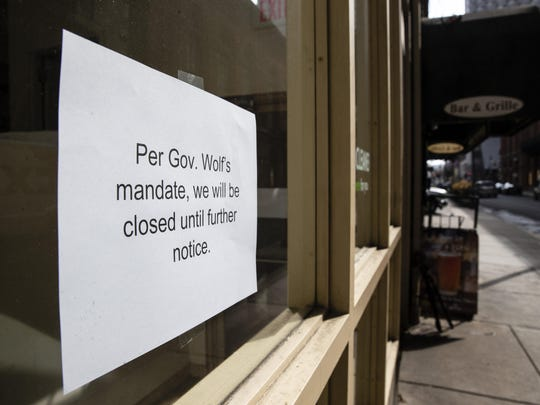 """A sign is posted in the window of a closed business in Philadelphia, Friday, March 20, 2020. Pennsylvania Gov. Tom Wolf directed all """"non-life-sustaining"""" businesses to close their physical locations late Thursday and said state government would begin to enforce the edict starting early Saturday. (AP Photo/Matt Rourke)"""