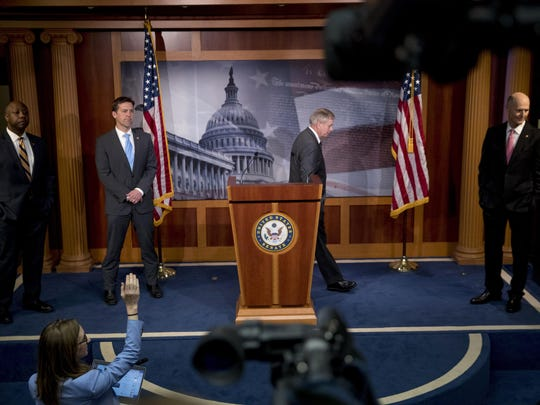 "Sen. Lindsey Graham, R-S.C., center, accompanied by Sen. Tim Scott, R-S.C., left, Sen. Ben Sasse, R-Neb., second from left, and Sen. Rick Scott, R-Fla., right, steps away from a podium during a news conference about the coronavirus relief bill on Capitol Hill in Washington, Wednesday, March 25, 2020. Senators discussed what they are calling a ""drafting error"" in the 2 trillion dollar stimulus bill. (AP Photo/Andrew Harnik)"