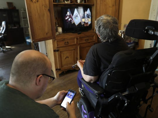 In this Tuesday, April 28, 2020, photo Zach Stafford, left, checks the news on his phone while sitting alongside his mother, Debra Mize, as they watch a livestream of the daily coronavirus briefing by Illinois Gov. J.B. Pritzker on the television in Belleville, Ill. The pair say they are consuming hours of news a day in various formats about the coronavirus. Americans are grappling with an essential question as they try to get the information they need to stay safe during the coronavirus crisis: Whom do you trust? (AP Photo/Jeff Roberson)