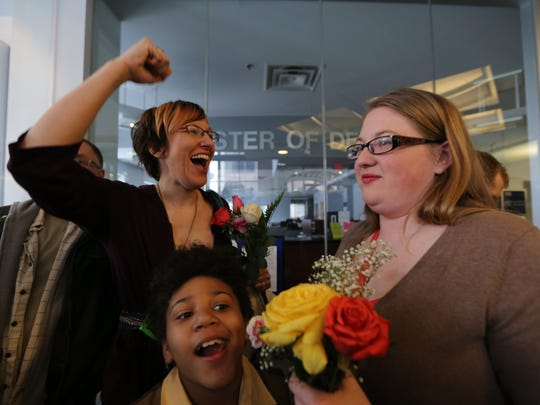 Maesie Secord and Debbie Dolney waiting to marry in 2014. With them is their daughter Olivia.