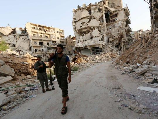 Rebel fighters walk in front of damaged buildings in Karam al-Jabal neighborhood of Aleppo