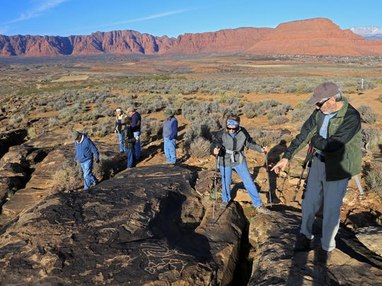 Hikers view some of the petroglyphs at the Land Hill