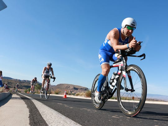 Athletes race during the bike portion of the Ironman 70.3 St. George on Saturday, May 3, 2014. The popular Ironman, an annual event hosted each May since 2010, is now scheduled to continue through 2020 after a new agreement was reached between Ironman and local officials.