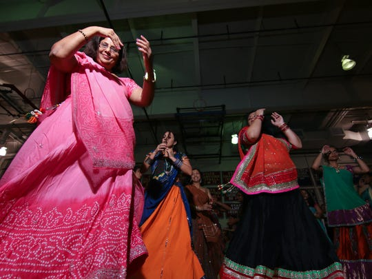 Female members of the Indian community participate in the Navrati (Garba) dance Friday, Oct. 3, 2014, at Christiana High School near Newark.