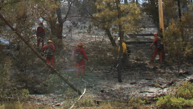 Firefighters work fire lines on the Timberon Fire that burned 268-acres.