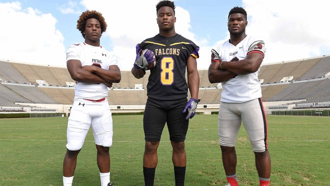 Running backs (from left) Stephon Huderson of Petal, Kylin Hill of Columbus and Cam Akers of Clinton post for pictures at the Dandy Dozen photo shoot on Monday, July 25, 2016, in Mississippi Veterans Memorial Stadium in Jackson, Miss.