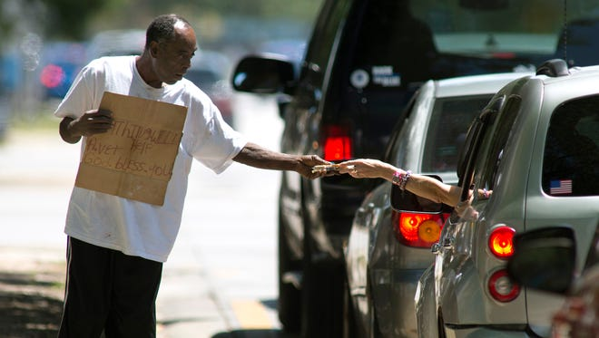 A driver hands money to James McCorvey on April 26, 2017, as he walks near the intersection of Palafox and Garden streets in Pensacola.