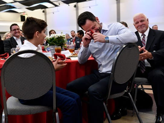 Parker Seago (left) watches his father Shaun Seago wipe his eyes during the luncheon at the First Financial Bankshares annual meeting Tuesday. The Seago family were among the First Financial employees who were impacted by Hurricane Harvey last year and were recognized during the luncheon.