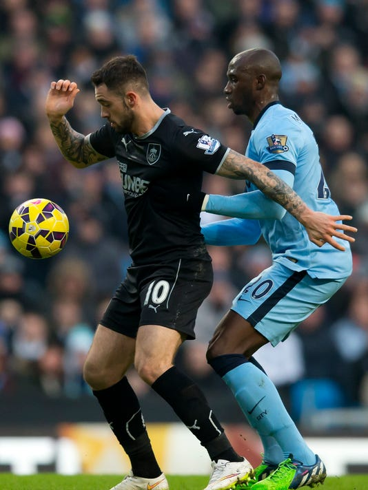 Manchester City's Eliaquim Mangala fights for the ball against Burnley's Danny Ings during the English Premier League soccer match between Manchester City and Burnley at the Etihad Stadium, Manchester, England, Sunday, Dec. 28, 2014. (AP Photo/Jon Super)