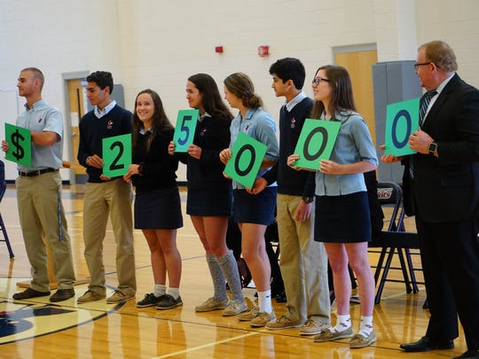Newark Charter High School students (from left) Jack Sharpe, Jake Schreiber, Jessica Trent, Taylor Wilson, Sarah Fylak, Rohan Kanchana, and Jada Mitchell hold up the dollar amount that Tami Lunsford, a teacher at Newark Charter School, received for the Milken Educator Award. It was presented to her during a school assembly Wednesday.