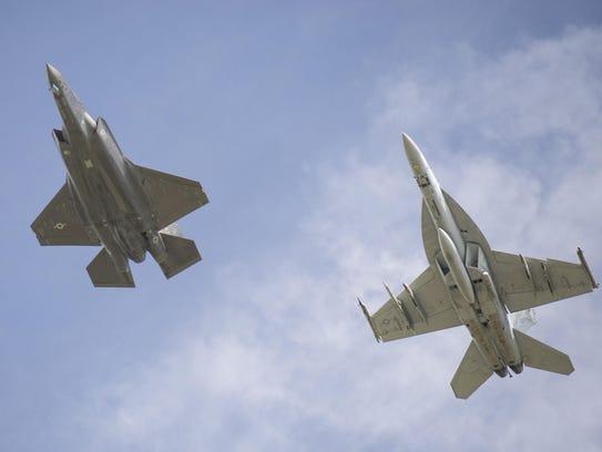 An F-35A Lightning II and an FA-18 Super Hornet fly