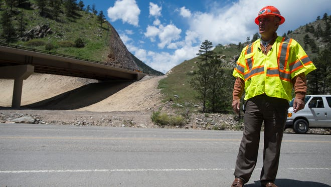 "Colorado Department of Transportation region 4 director Johnny Olson stands on the old road section known as ""The Horseshoe"" while the new section of highway spans the bridge behind him while talking to members of local media on Monday, May 21, 2018, on Highway 34 between Loveland and Estes Park, Colo."