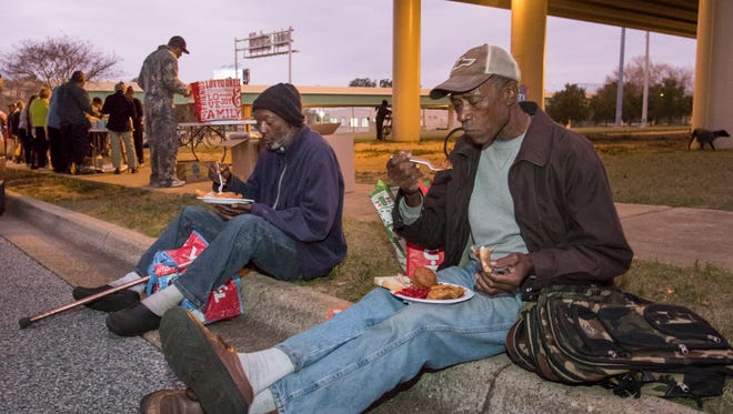 Otis Womack, left, and Chester Johnson enjoy their dinner during the weekly meal served under the I-110 overpass on Lee Street each Thursday in downtown Pensacola.