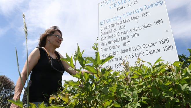 Fern Smazal smiles while posing next to the sign depicting the approximate location of the Castner-Mack Cemetery, the oldest cemetery in Loyal, June 24, 2016. Smazal takes issue with the way the burial ground is being treated by the farmer who owns the land.