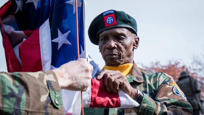 Vietnam veteran Walter Edwards of West Chester holds the flag for the presentation and posting of colors during the Veterans Day program hosted by Vietnam Veterans of America Chapter 10 Saturday, Nov. 11, 2017, at the Vietnam Memorial in Eden Park.