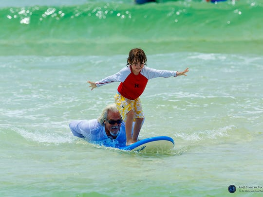 Volunteer Mike Stone helps a young one learn how to surf.
