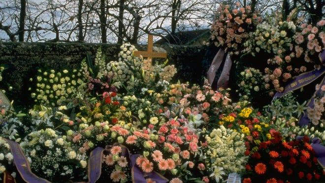A modest wooden cross with Audrey Hepburn in script marks her gravesite in Tolochenaz, Switzerland.