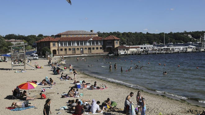 People, including many from Illinois, enjoy the beach Tuesday in Lake Geneva, Wis.