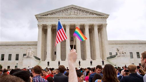 In this Friday file photo, a man holds a U.S. and a rainbow flag outside the Supreme Court in Washington after the court legalized gay marriage nationwide.