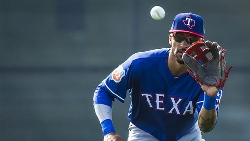 Texas Rangers outfielder Ian Desmond catches a fly ball while participating in a fielding drill during a spring baseball workout at the team's training facility, Monday.