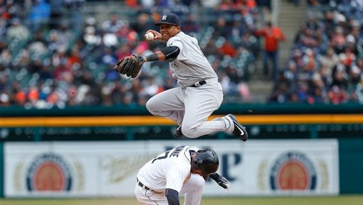 Detroit Tigers' Andrew Romine (17) slides safely into second base as New York Yankees second baseman Starlin Castro throws to first base on a James MCann ground ball in the eighth inning of a baseball game, Friday, April 8, 2016, in Detroit. Romine was originally called out on the play but was overturned on video replay. McCann was out at first base.