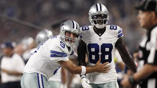 In this Sept. 13, 2015, file photo, Dallas Cowboys quarterback Tony Romo (9) and wide receiver Dez Bryant (88) react during the first half of an NFL football game against the New York Giants in Arlington, Texas. Both are anxious to get on the field together after injuries kept them apart most of last season, when Dallas slid from first to worst in the NFC East.
