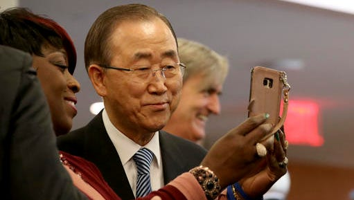 United Nations Secretary-General Ban Ki-moon, poses for a selfie photo with one of his staff members on his last day at the U.N. headquarters on Friday, Dec. 30, 2016.