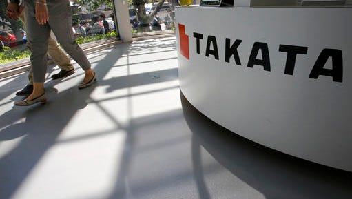 FILE - In this May 4, 2016, file photo, visitors walk by a Takata Corp. desk at an automaker's showroom in Tokyo.  The Justice Department is planning to announce a criminal penalty against the Japanese air bag maker  as part of its investigation into the company's defective air bag inflators. The department has scheduled a news conference Friday, Jan. 13, 2017 in Detroit to make the announcement.