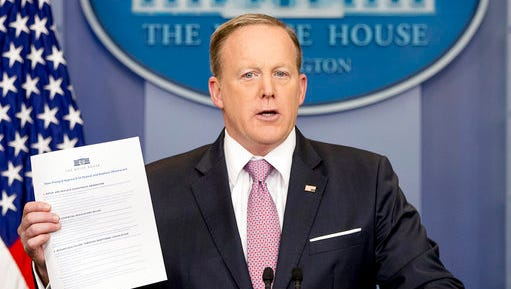 """White House press secretary Sean Spicer holds up a Trump Administration document to """"repeal and replace Obamacare"""" as he talks to the media during the daily press briefing at the White House in Washington, Friday, March 10, 2017."""