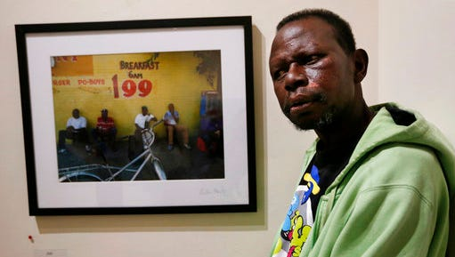 In this April 11, 2017 photo, William Hardy, who is homeless, poses for a portrait in front of one of his photos, at the Lemieux Galleries, in New Orleans. Hardy was given a camera and has sold prints in the gallery. His works are part of an exhibit by artists, who are or were previously homeless, currently on display at LeMieux Galleries in New Orleans' Arts District.