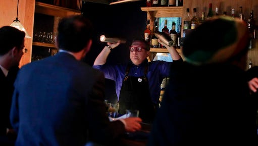 Coup co-founder Sother Teague mixes drinks for customers shortly after opening the bar, Tuesday, April 25, 2017, in New York. As a response to the Trump Administration, the bar in Manhattan's East Village offers patrons the chance to put their money where their politics are by earmarking where the profits should go from a range of liberal or progressive options like the American Civil Liberties Union or Planned Parenthood.