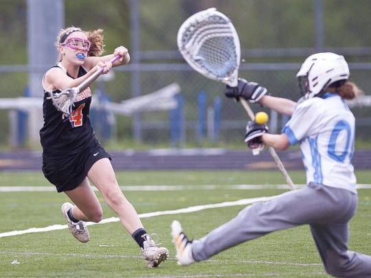 Middlebury's Emily Laframboise, left, fires a goal past South Burlington goalie Claire Phillips during Tuesday's high school girls lacrosse game in South Burlington.