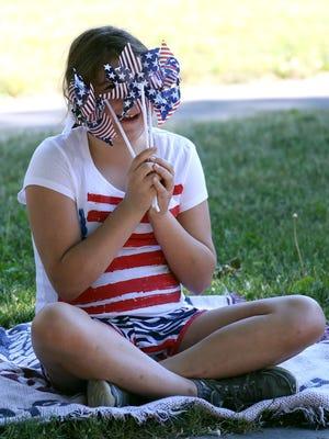 Katy Herrmann, 9, of Macedon, peeks through toy windmills  during the Fairport July 4th parade.