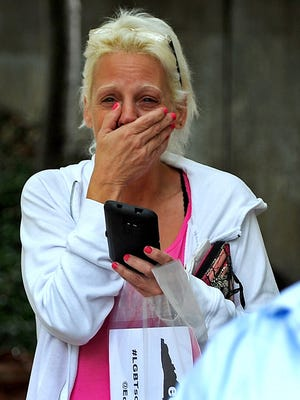 Lynda Johnson, center, cries as she watches her daughter Oct. 13, 2014, marry Jana Downs outside the Mecklenburg County courthouse.