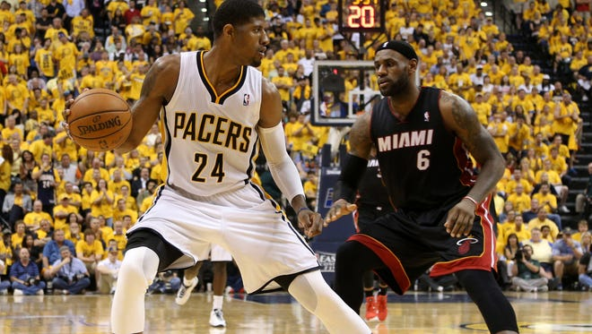 Indiana Pacers forward Paul George (24) works around the defense of Miami Heat forward LeBron James (6) during the fourth quarter in game five of the Eastern Conference Finals of the 2014 NBA Playoffs at Bankers Life Fieldhouse.  Indiana defeats Miami 93-90.