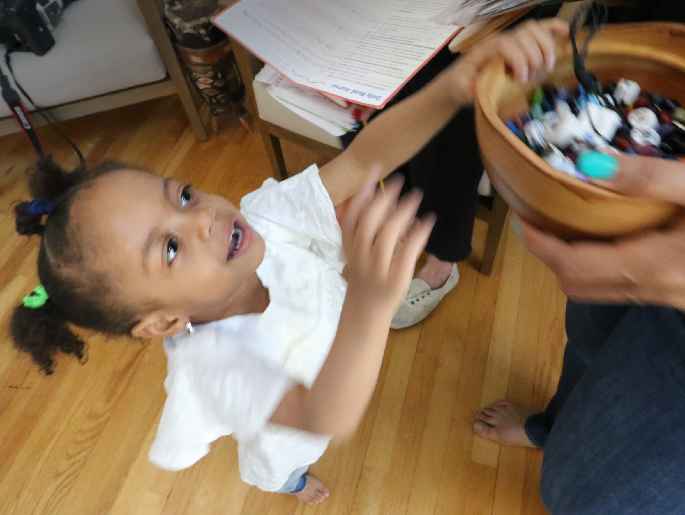 Evelyn Islam, 2, reaches for the bowl that her mother