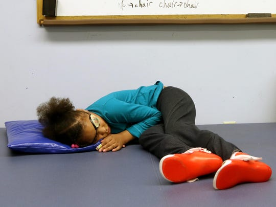 China Kinebrew, 6, takes a short break during her occupational therapy appointment with Cincinnati Children's Hospital Medical Center Tuesday Dec. 8, 2015. China was shot July 6, 2015 in Avondale. The shooting left her paralyzed and without her left eye.