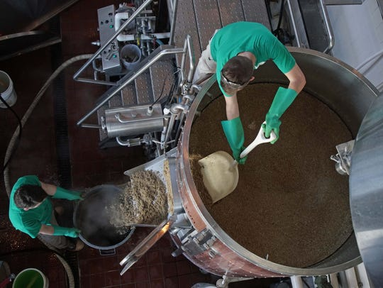 In this file photo, Alex VanderLek, an assistant brewer at Iron Hill Brewery on the Riverfront, holds a trash can in place as Warren Skopowski shovels grain out of a mash tun while making a batch of Ore House IPA. Iron Hill is coming to Rehoboth in May 2018.