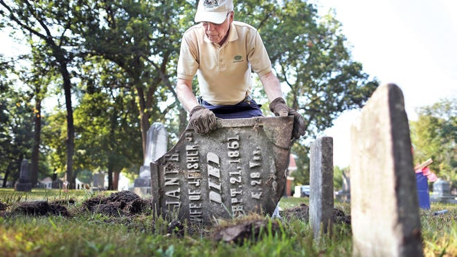 John Kalkirtz carefully works to turn over a gravestone he found broken and buried underneath several inches of soil at Oakwood Cemetery in Beloit, Wis. Kalkirtz has volunteered for the last two years to help preserve fallen and broken grave markers at Oakwood and Eastlawn cemeteries, restoring more than 50 grave markers.
