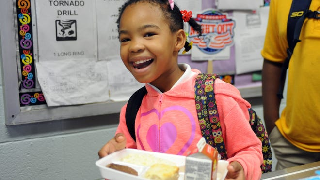 Second-grader Zarieah Silas, 8, grabs a hot plate breakfast before school starts at Rowan Elementary. Hattiesburg Public School District nutrition officials are working to encourage more students to eat school breakfast.