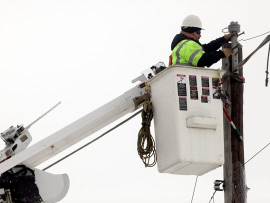 A MidAmerican Energy Co. worker tackles an electrical power line project in this file photo.