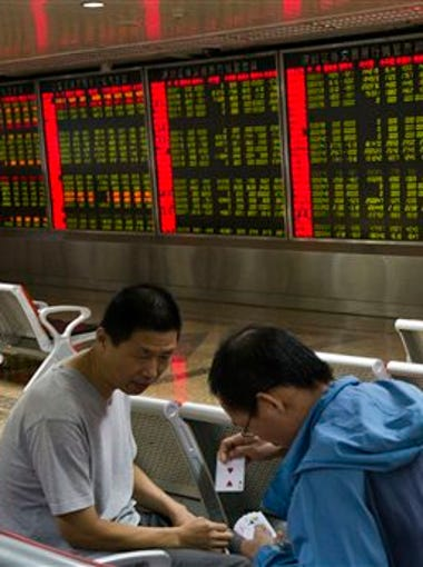 Investors play a card game near electronic boards displaying stock prices in Beijing, Friday, Aug. 21, 2015.  Asian stocks fell further Friday after a survey showed Chinese manufacturing weakened this month. Stock markets around the world suffered further big declines Friday amid concerns over the Chinese economy and renewed uncertainty over Greece following the decision by Alexis Tsipras to resign as prime minister.