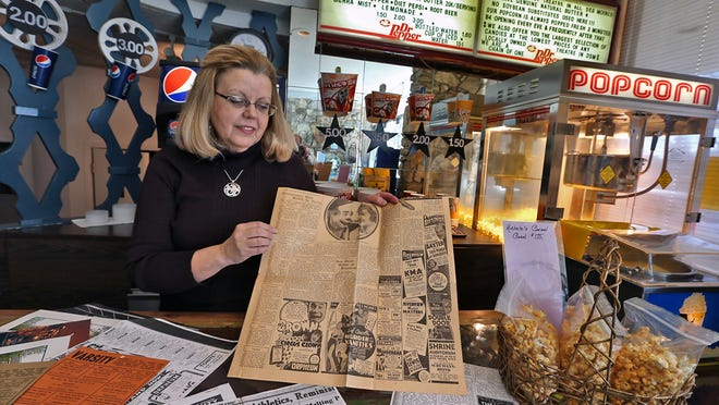Denise Mahon, owner of the Varsity Theatre, looks at a news paper from 1935 with movie ads, including ads for the Varsity. The movie theater is at 25th Street and University Avenue in Des Moines.