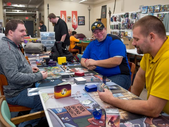 From left to right: Michael Thompson, Kacey Tucker, and Randall Sword play the board game Magic The Gathering Planechase Anthology at Knight's Comics & Games  in Henderson, Ky., on Saturday, Nov. 11, 2017. The three enjoy coming to the store on weekends and say the atmosphere is always positive and welcoming.