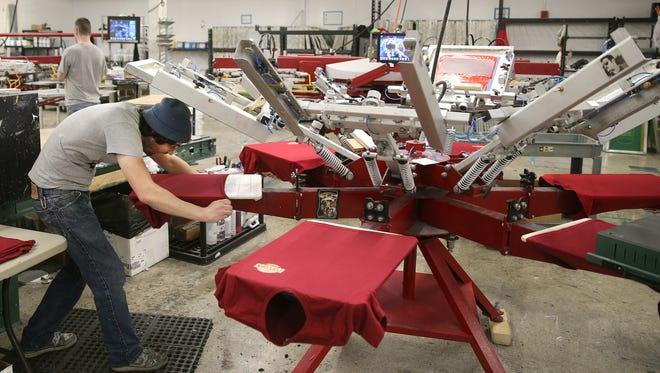 Harley Barletta loads shirts on a manual press to be printed at Crazy Dog T Shirts.